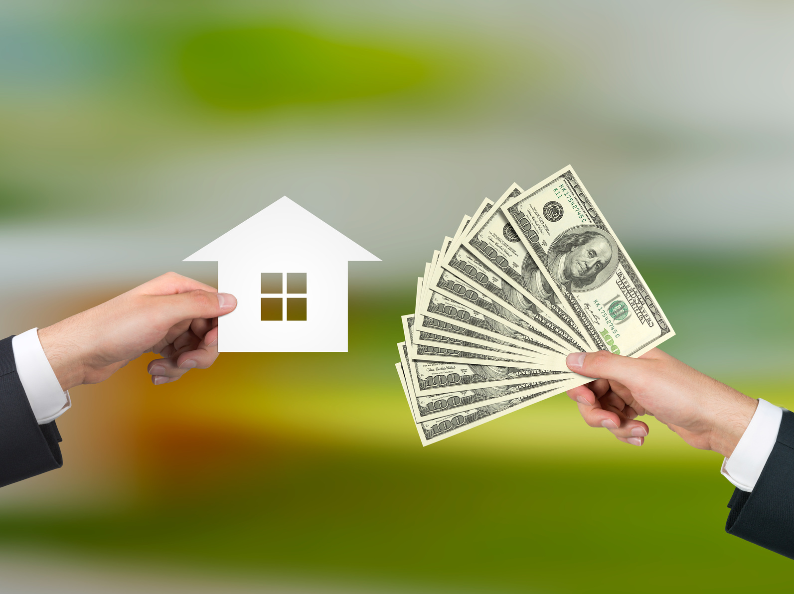 hand giving money for housing on a gray background
